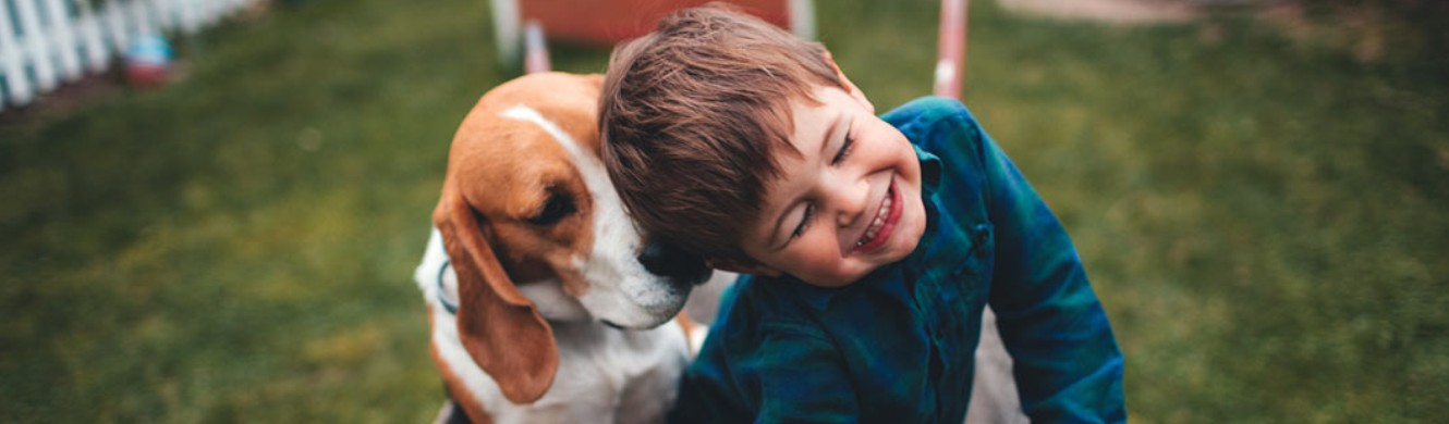 Boy laughing with his eyes shut as he plays with dog
