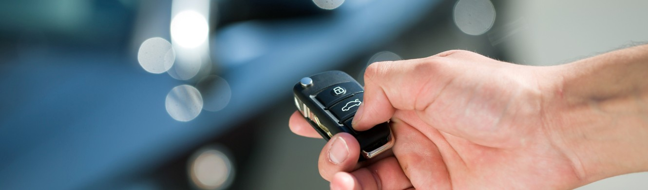 hand with car keys stand by car